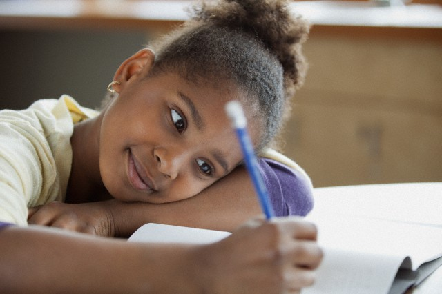 28 Apr 2012 --- Pretty, young student writing at desk. --- Image by © Hero Images/Corbis