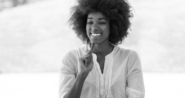 Portrait of beautiful smiling black woman with pen in arm